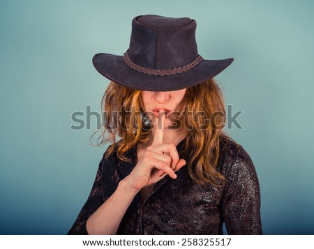 A young woman wearing a cowboy hat is gesturing hush by putting her finger on her lips