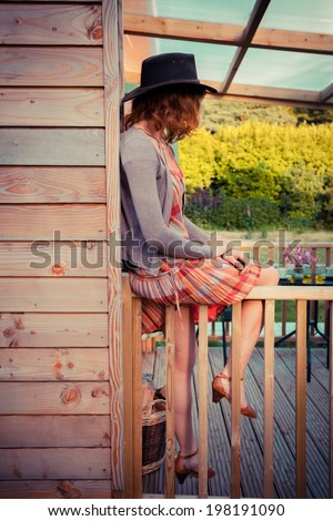 A young woman wearing a cowboy hat is sitting on the porch of a cabin - stock photo