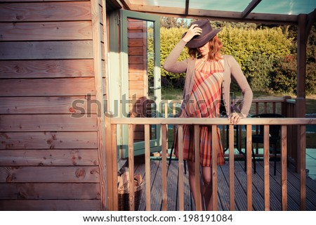 A young woman wearing a cowboy hat is standing on the porch of a cabin - stock photo