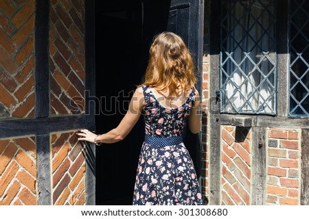 A young woman wearing a dress is opening a door and is entering an old rustic farmhouse in the summer - stock photo