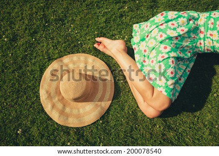 A young woman wearing a dress is sleeping on the grass with a hat next to her - stock photo
