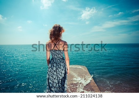 A young woman wearing a dress is standing by the ocean on a sunny day - stock photo