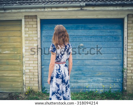 A young woman wearing a dress is standing outside a garage - stock photo