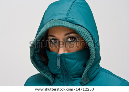 A young woman wearing a green winter coat using the hood to cover her head so that only her eyes are visible - stock photo
