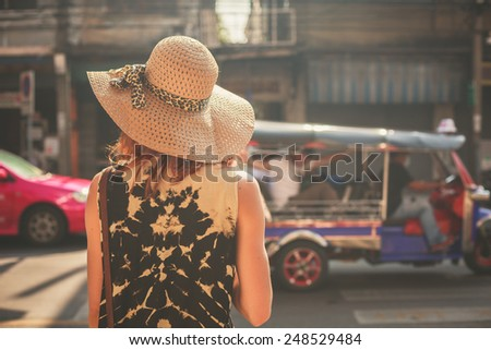 A young woman wearing a hat is walking in the streets of an asian country - stock photo