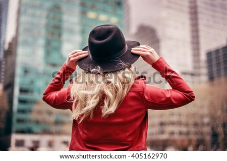 A young woman wearing a hat is walking in the streets of New York City - stock photo