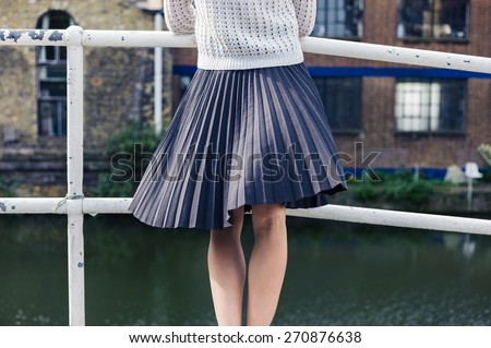 A young woman wearing a skirt is standing on a bridge by a canal and is relaxing whilst looking at an old building - stock photo