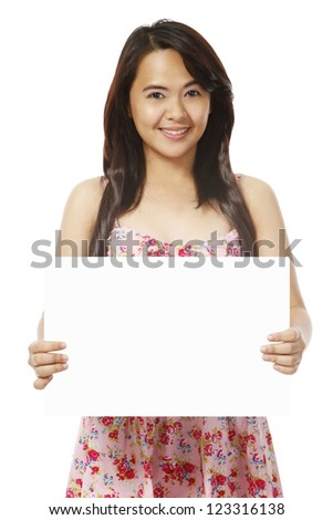 A young woman wearing a summer dress and holding a blank message (on white). - stock photo