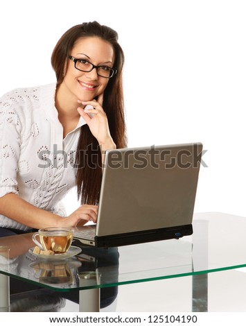 A young woman wearing glasses in front of a laptop, isolated on white