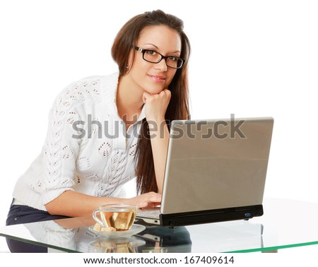 A young woman wearing glasses in front of a laptop, isolated on white.