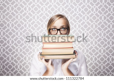 A young woman wearing glasses peers over a tall stack of books. - stock photo