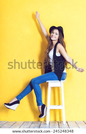 A young woman wearing hat on a chair in studio - stock photo