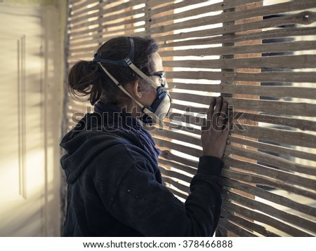 A young woman wearing protective workwear is peeping through an old wattle and daub wall