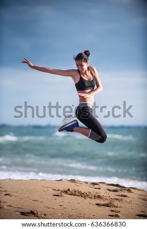 A young woman wearing sportswear is jumping on the beach, the ocean at the background