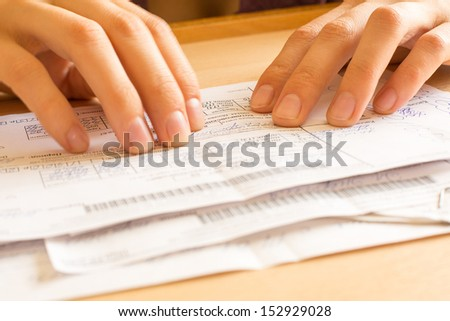 A young woman while sorting her old receipts  - stock photo