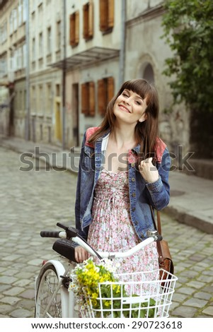A young woman with a city bike. The woman, Bicycle, flowers, basket. Young woman in dress and jacket. Summer mood. Walk the old town. Youth, serenity, and romance. Street portrait. Retro look. - stock photo