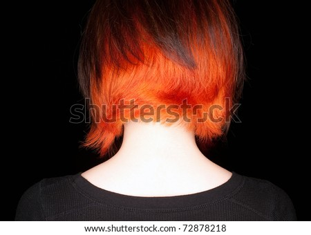 A young woman with a funky hair cut and color of orange and dark brown on a black background.