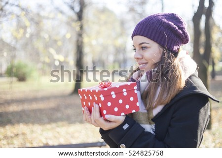 A young woman with a gift in their hands, Selective focus and small depth of field, Lens flare