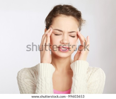 A young woman with a headache holding head, isolated on white background