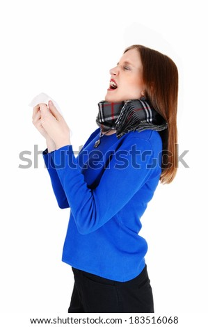 A young woman with a heavy scarf around her neck holding a tissue and sneezing, for white background.  - stock photo