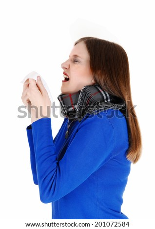 A young woman with a heavy scarf around her neck holding a tissue and sneezing, isolated for white background.  - stock photo