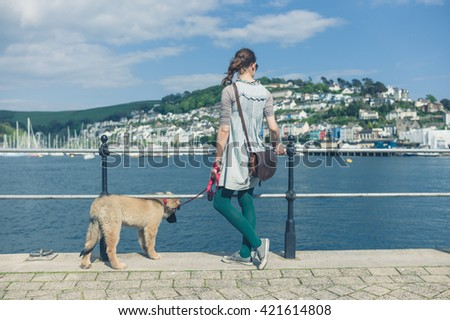 A young woman with a Leonberger puppy is standing by the river in a small town on a sunny day - stock photo