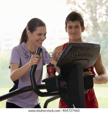 A young woman with a personal trainer - stock photo