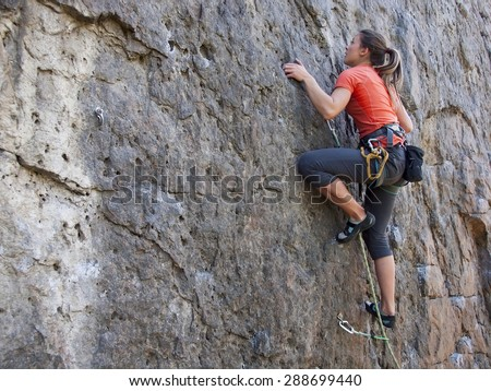 A young woman with a rope engaged in the sports of rock climbing on the rock. - stock photo