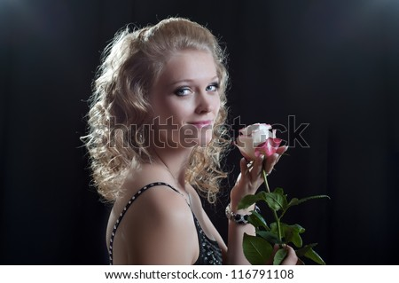 A young woman with a rose,  black background - stock photo