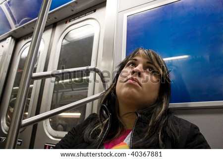 A young woman with a sad look on her face riding on the subway.