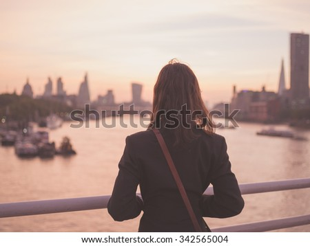 A young woman with a shoulderbag is standing on a bridge and is admiring the sunrise over the London skyline - stock photo