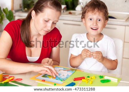 A young woman with a son having fun playing in clay