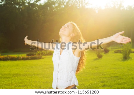 A young woman with arms outstretched in the sun - stock photo