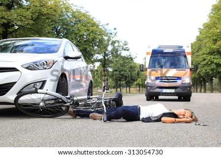 A Young Woman with bicycle accident and coming ambulance car - stock photo