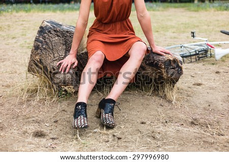 A young woman with bruises on her leg is sitting on a log outside, there is a bicycle in the background - stock photo