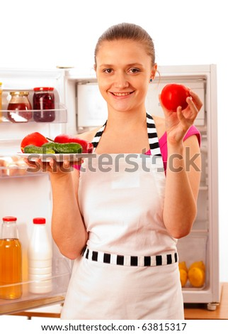 A young woman with fresh vegetables on a white plate smiling to the camera, preparing to cook. - stock photo