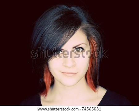 A young woman with funky hair in black and red-orange on a black background.