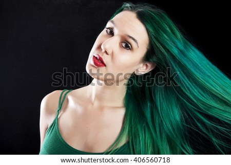 A young woman with long, forest green hair.  Shot on black background.