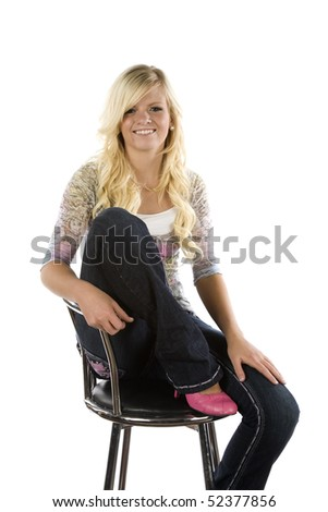 A young woman with pink shoes sitting on a metal chair.