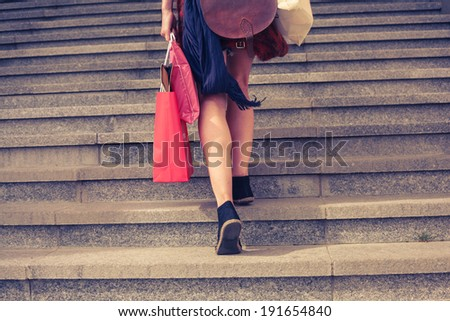 A young woman with shopping bags is walking up the stairs outside at sunset - stock photo