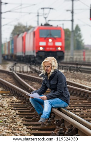 a young woman with suicidal thoughts sitting on a track. considers suicide note in his hand and thinks about her suicide. - stock photo
