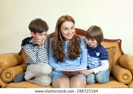 a young woman with two children reading a book - stock photo