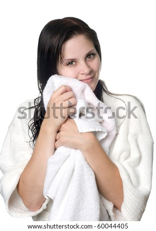 A young woman with wet hair in white robe toweling off after a shower. - stock photo