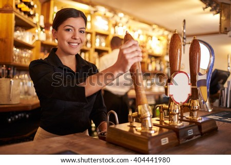 A young woman working behind a bar looking to camera, horizontal - stock photo