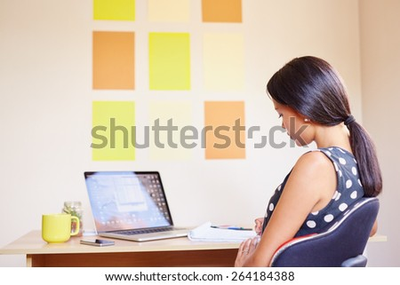 A young woman working on her laptop in her office