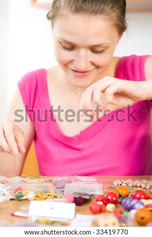 A young woman working with her beads, making jewels. - stock photo