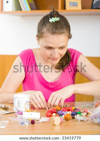 A young woman working with her beads , making jewels. - stock photo