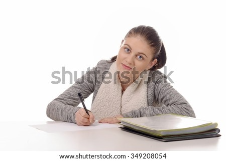 a young woman writing on her desk isolated on a white background