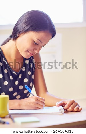 A young woman writing while sitting in her office