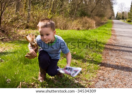A young 4 year old Caucasian boy is picking up garbage on the side of the road to do his share for helping ecology and environmental issues. - stock photo